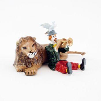 clown jouant de la trompette assis devant un lion