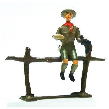 scout assis sur barrière cirant chaussure